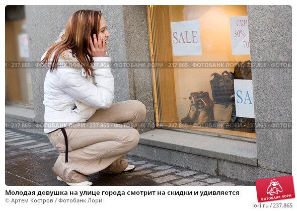 Молодая девушка на улице города смотрит на скидки и удивляется, фото № 237865, снято 28 марта 2008 г. (c) Артем Костров / Фотобанк Лори