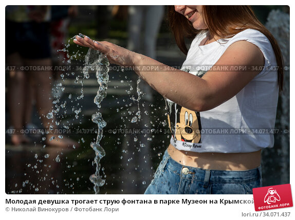 Молодая девушка трогает струю фонтана в парке Музеон на Крымской набережной во время изнуряющей жары в городе Москве, Россия. Редакционное фото, фотограф Николай Винокуров / Фотобанк Лори