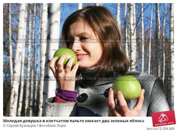Купить «Молодая девушка в клетчатом пальто нюхает два зеленых яблока», фото № 2159369, снято 31 октября 2010 г. (c) Сергей Кузнецов / Фотобанк Лори