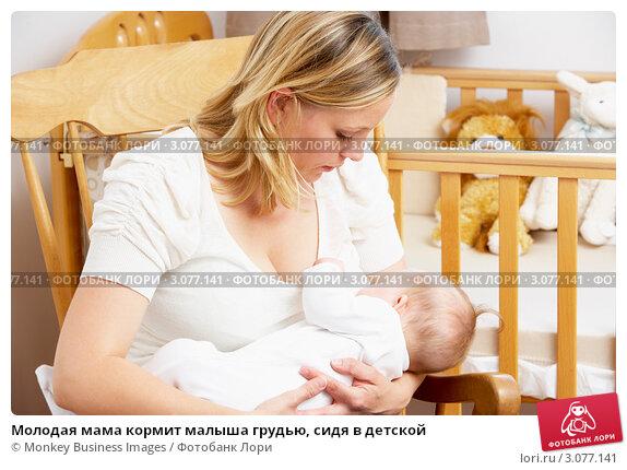 Купить «Молодая мама кормит малыша грудью, сидя в детской», фото № 3077141, снято 11 июня 2009 г. (c) Monkey Business Images / Фотобанк Лори