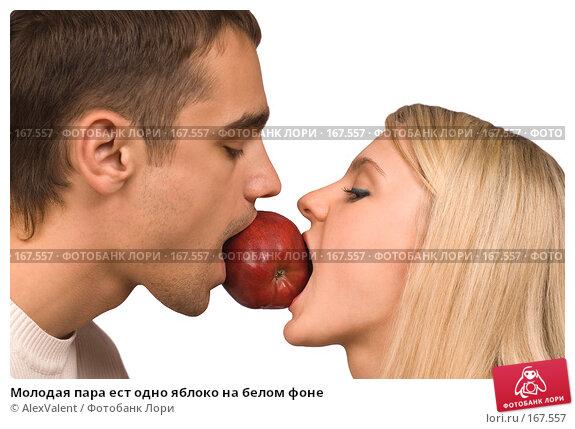 Купить «Молодая пара ест одно яблоко на белом фоне», фото № 167557, снято 24 марта 2018 г. (c) AlexValent / Фотобанк Лори