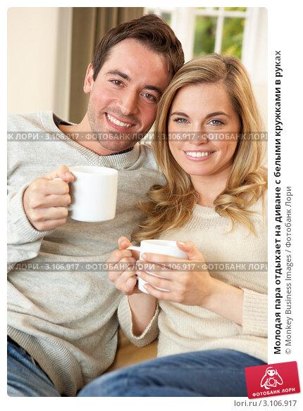 Купить «Молодая пара отдыхает на диване с белыми кружками в руках», фото № 3106917, снято 11 ноября 2010 г. (c) Monkey Business Images / Фотобанк Лори