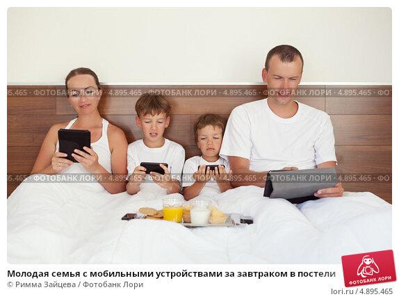 Молодая семья с мобильными устройствами за завтраком в постели. Стоковое фото, фотограф Римма Зайцева / Фотобанк Лори