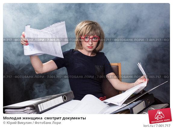 Купить «Молодая женщина  смотрит документы», фото № 7001717, снято 6 февраля 2015 г. (c) Юрий Викулин / Фотобанк Лори