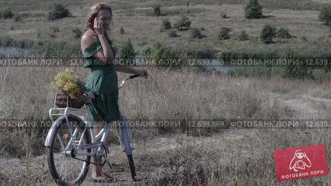 Молодая женщина стоит на проселочной дороге с велосипедом и разговаривает по телефону. Стоковое видео, видеограф Земсков Андрей  Владимирович / Фотобанк Лори