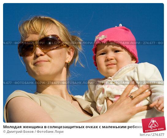 Молодая женщина в солнцезащитных очках с маленьким ребенком на руках на фоне голубого неба (2), фото № 274677, снято 3 июня 2006 г. (c) Дмитрий Боков / Фотобанк Лори