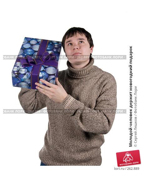 Молодой человек держит новогодний подарок, фото № 262889, снято 25 ноября 2007 г. (c) Сергей Лешков / Фотобанк Лори