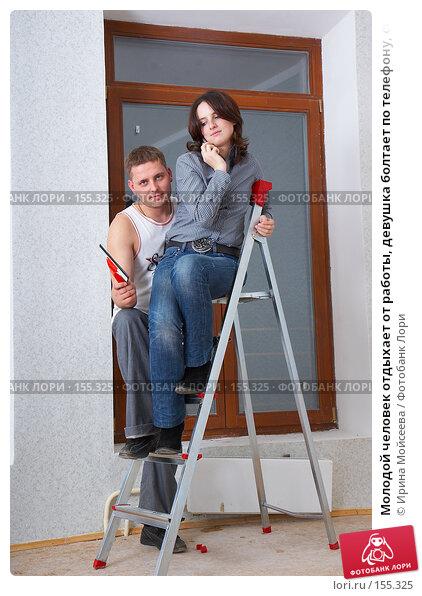 Молодой человек отдыхает от работы, девушка болтает по телефону, сидя на стремянке, фото № 155325, снято 5 декабря 2007 г. (c) Ирина Мойсеева / Фотобанк Лори