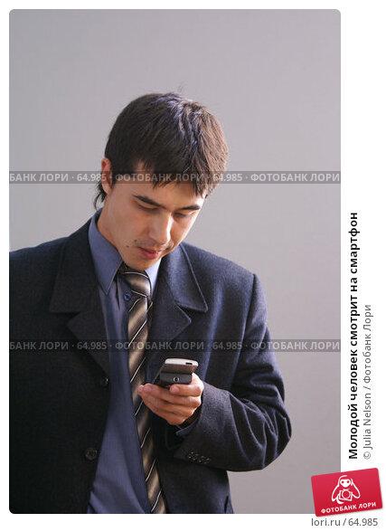 Молодой человек смотрит на смартфон, фото № 64985, снято 22 июля 2007 г. (c) Julia Nelson / Фотобанк Лори