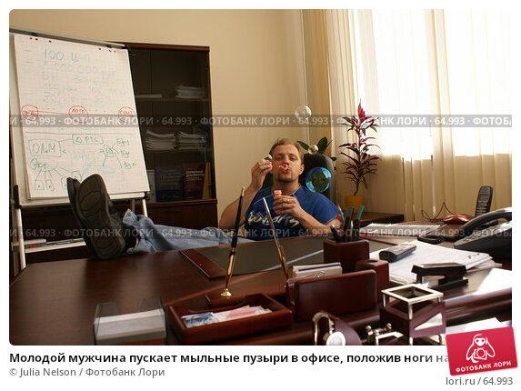 Молодой мужчина пускает мыльные пузыри в офисе, положив ноги на стол, фото № 64993, снято 22 июля 2007 г. (c) Julia Nelson / Фотобанк Лори