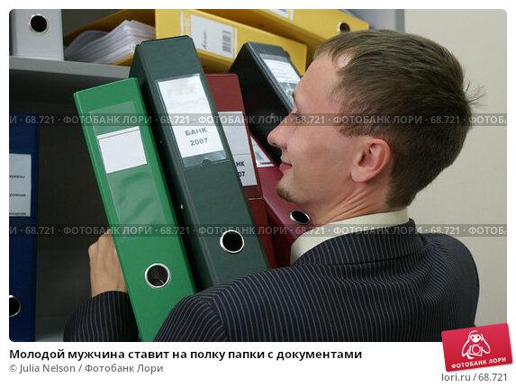 Молодой мужчина ставит на полку папки с документами, фото № 68721, снято 29 июля 2007 г. (c) Julia Nelson / Фотобанк Лори