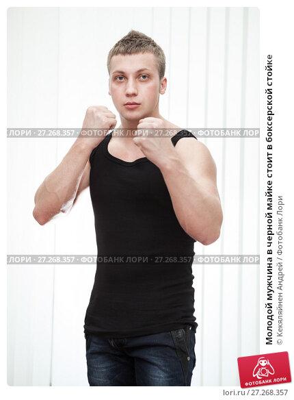 Купить «Молодой мужчина в черной майке стоит в боксерской стойке», фото № 27268357, снято 4 марта 2012 г. (c) Кекяляйнен Андрей / Фотобанк Лори