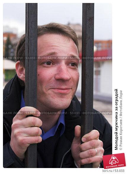 Молодой мужчина за оградой, фото № 53033, снято 1 мая 2007 г. (c) Роман Коротаев / Фотобанк Лори