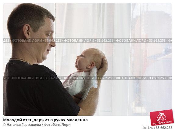 Молодой отец держит в руках младенца. Стоковое фото, фотограф Наталья Гармашева / Фотобанк Лори