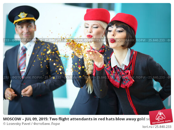 Купить «MOSCOW – JUL 09, 2015: Two flight attendants in red hats blow away gold sequins with palms at DME RUNVAY in Domodedovo», фото № 25840233, снято 9 июля 2015 г. (c) Losevsky Pavel / Фотобанк Лори