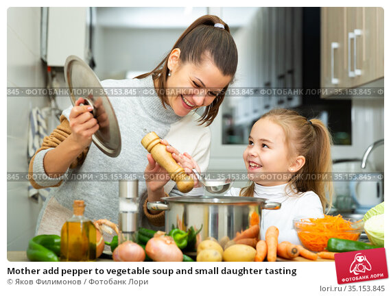 Mother add pepper to vegetable soup and small daughter tasting. Стоковое фото, фотограф Яков Филимонов / Фотобанк Лори