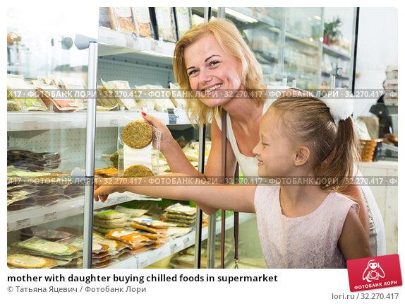 Купить «mother with daughter buying chilled foods in supermarket», фото № 32270417, снято 17 октября 2019 г. (c) Татьяна Яцевич / Фотобанк Лори