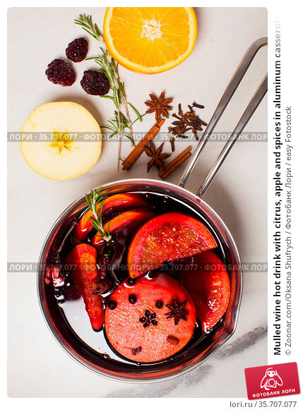 Mulled wine hot drink with citrus, apple and spices in aluminum casserole... Стоковое фото, фотограф Zoonar.com/Oksana Shufrych / easy Fotostock / Фотобанк Лори