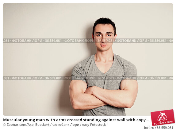 Muscular young man with arms crossed standing against wall with copy... Стоковое фото, фотограф Zoonar.com/Axel Bueckert / easy Fotostock / Фотобанк Лори
