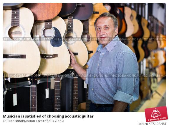 Купить «Musician is satisfied of choosing acoustic guitar», фото № 27102481, снято 18 сентября 2017 г. (c) Яков Филимонов / Фотобанк Лори