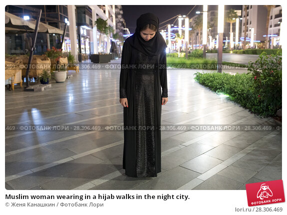 Купить «Muslim woman wearing in a hijab walks in the night city.», фото № 28306469, снято 25 марта 2018 г. (c) Женя Канашкин / Фотобанк Лори