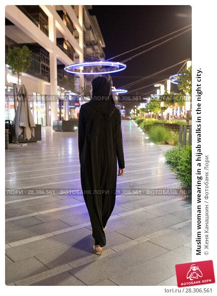Купить «Muslim woman wearing in a hijab walks in the night city.», фото № 28306561, снято 25 марта 2018 г. (c) Женя Канашкин / Фотобанк Лори