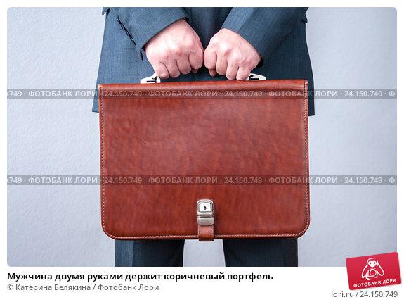 Купить «Мужчина двумя руками держит коричневый портфель», фото № 24150749, снято 21 октября 2016 г. (c) Катерина Белякина / Фотобанк Лори