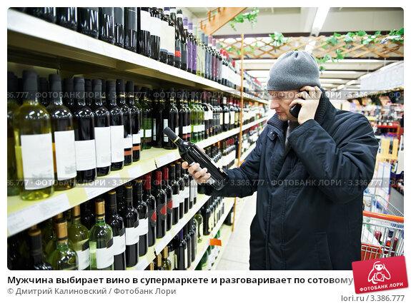Мужчина выбирает вино в супермаркете и разговаривает по сотовому телефону, фото № 3386777, снято 31 декабря 2011 г. (c) Дмитрий Калиновский / Фотобанк Лори