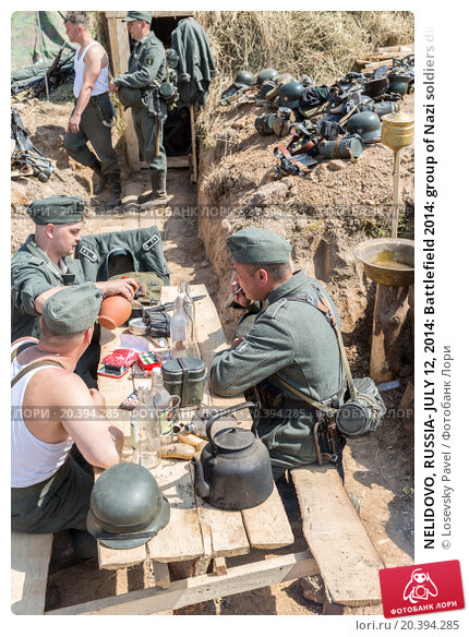 Купить «NELIDOVO, RUSSIA- JULY 12, 2014: Battlefield 2014: group of Nazi soldiers dine at a table in the trenches», фото № 20394285, снято 12 июля 2014 г. (c) Losevsky Pavel / Фотобанк Лори