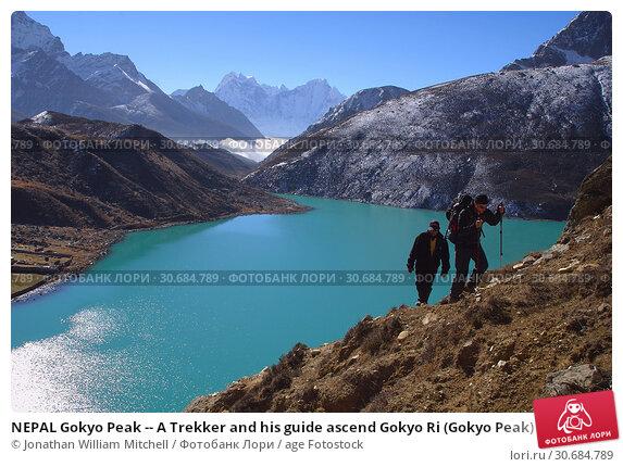 Купить «NEPAL Gokyo Peak -- A Trekker and his guide ascend Gokyo Ri (Gokyo Peak) with the third lake of the spectacular Gokyo valley in the background. This valley...», фото № 30684789, снято 19 августа 2019 г. (c) age Fotostock / Фотобанк Лори