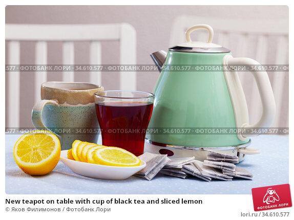 New teapot on table with cup of black tea and sliced lemon. Стоковое фото, фотограф Яков Филимонов / Фотобанк Лори