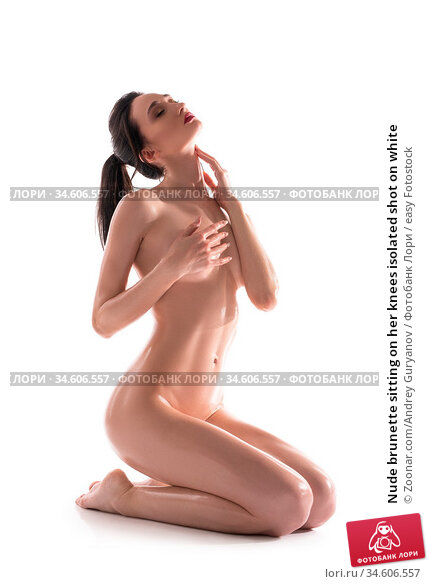 Nude brunette sitting on her knees isolated shot on white. Стоковое фото, фотограф Zoonar.com/Andrey Guryanov / easy Fotostock / Фотобанк Лори