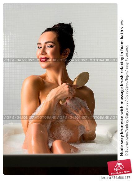 Nude sexy brunette with massage brush relaxing in foam bath view. Стоковое фото, фотограф Zoonar.com/Andrey Guryanov / easy Fotostock / Фотобанк Лори