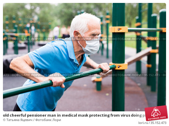 old cheerful pensioner man in medical mask protecting from virus doing physical exercises on sports equipped playground. Стоковое фото, фотограф Татьяна Яцевич / Фотобанк Лори
