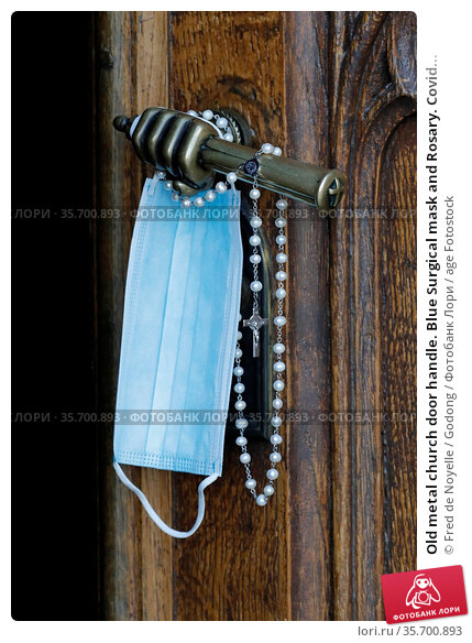 Old metal church door handle. Blue Surgical mask and Rosary. Covid... Стоковое фото, фотограф Fred de Noyelle / Godong / age Fotostock / Фотобанк Лори