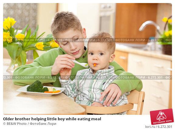 Купить «Older brother helping little boy while eating meal», фото № 6272301, снято 19 июля 2019 г. (c) BE&W Photo / Фотобанк Лори