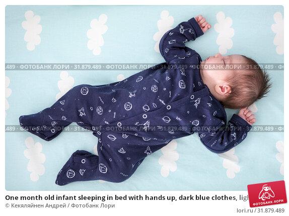 Купить «One month old infant sleeping in bed with hands up, dark blue clothes, light blue linen with clouds, full length», фото № 31879489, снято 22 июня 2019 г. (c) Кекяляйнен Андрей / Фотобанк Лори