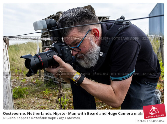 Oostvoorne, Netherlands. Hipster Man with Beard and Huge Camera making a photograph as a semi professional photographer. (2019 год). Редакционное фото, фотограф Guido Koppes / age Fotostock / Фотобанк Лори