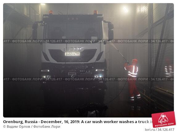 Купить «Orenburg, Russia - December, 16, 2019: A car wash worker washes a truck in a cargo car wash», фото № 34126417, снято 16 декабря 2019 г. (c) Вадим Орлов / Фотобанк Лори