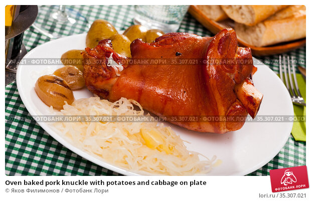 Oven baked pork knuckle with potatoes and cabbage on plate. Стоковое фото, фотограф Яков Филимонов / Фотобанк Лори