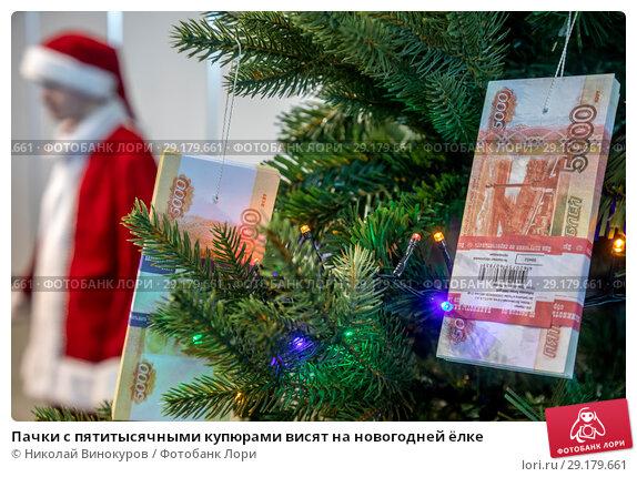Купить «Пачки с пятитысячными купюрами висят на новогодней ёлке», фото № 29179661, снято 5 октября 2018 г. (c) Николай Винокуров / Фотобанк Лори
