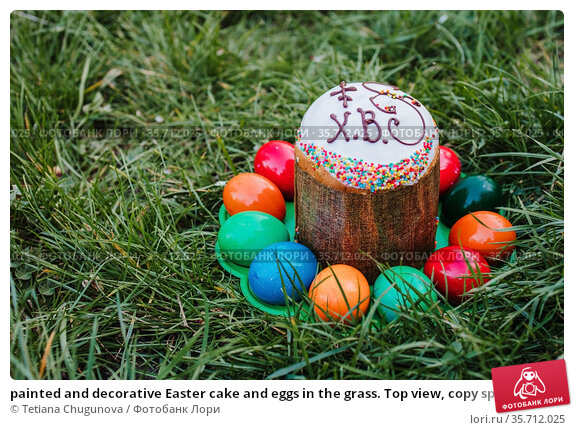 painted and decorative Easter cake and eggs in the grass. Top view, copy space. Стоковое фото, фотограф Tetiana Chugunova / Фотобанк Лори