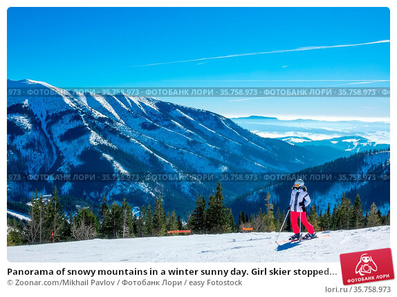 Panorama of snowy mountains in a winter sunny day. Girl skier stopped... Стоковое фото, фотограф Zoonar.com/Mikhail Pavlov / easy Fotostock / Фотобанк Лори