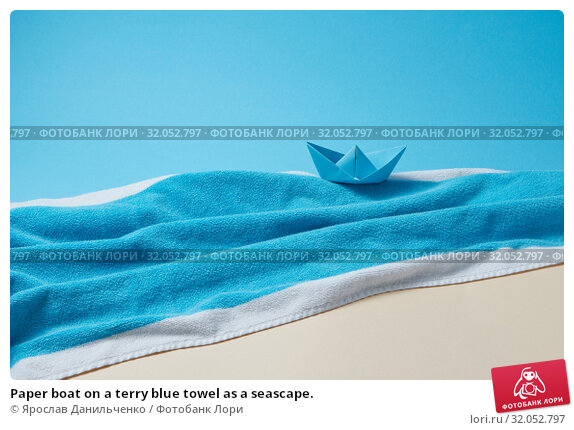 Paper boat on a terry blue towel as a seascape. Стоковое фото, фотограф Ярослав Данильченко / Фотобанк Лори