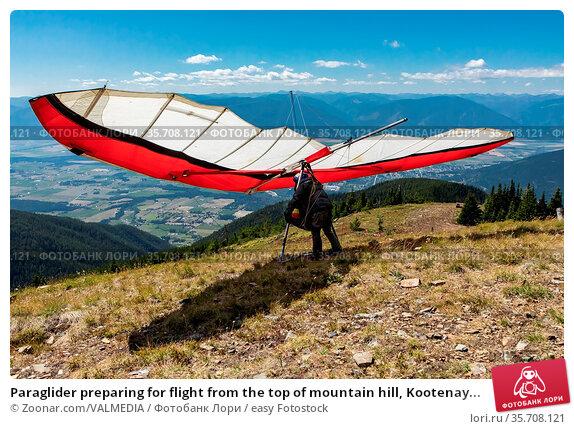 Paraglider preparing for flight from the top of mountain hill, Kootenay... Стоковое фото, фотограф Zoonar.com/VALMEDIA / easy Fotostock / Фотобанк Лори