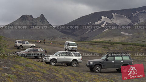 Parking extreme off-road expedition cars, SUV travelers at foot of volcano - popular travel destinations for climbing, hiking, observing wildlife. Kamchatka Peninsula. Редакционное видео, видеограф А. А. Пирагис / Фотобанк Лори