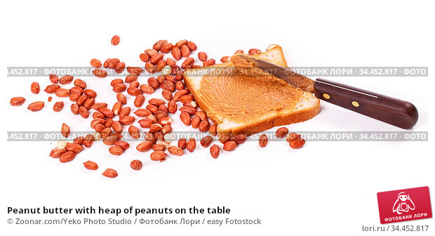 Peanut butter with heap of peanuts on the table. Стоковое фото, фотограф Zoonar.com/Yeko Photo Studio / easy Fotostock / Фотобанк Лори