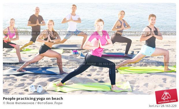 Купить «People practicing yoga on beach», фото № 28163229, снято 14 июня 2017 г. (c) Яков Филимонов / Фотобанк Лори