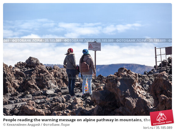 People reading the warning message on alpine pathway in mountains, the Teide peak, Tenerife island, Canary, Spain. Стоковое фото, фотограф Кекяляйнен Андрей / Фотобанк Лори