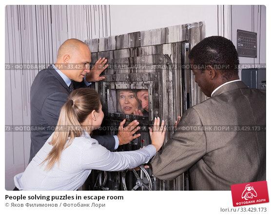 Купить «People solving puzzles in escape room», фото № 33429173, снято 29 января 2019 г. (c) Яков Филимонов / Фотобанк Лори